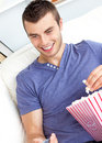 Positive man holding a remote and eating popcorn Stock Image
