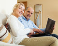 Positive mature couple with laptop in room at home Stock Photography