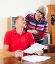 Positive mature couple looking financial documents in home Royalty Free Stock Photos
