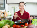 Positive mature woman cooking with skillet in domestic kitchen Stock Photography
