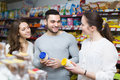 Positive people choosing tinned food young at supermarket Stock Photography
