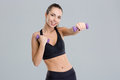 Positive pretty fitness girl exercising with dumbbells over grey background Stock Photo