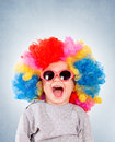 Positive small clown child with sunglasses and wig isolated on blue background Stock Photos