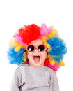 Positive small clown child with sunglasses and wig isolated on white background Royalty Free Stock Photography