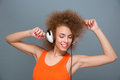 Positive smiling beautiful girl listening to music and dancing relaxed modern curly in orange top with eyes closed Stock Photography