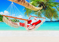 Positive smiling Christmas Santa Claus relax in hammock at island sandy ocean beach Royalty Free Stock Photo