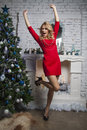 Positive winner Girl in red party dress near new year tree