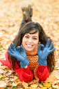 Positive woman approving on autumn lying down leaves with okay sing with hands in gloves happy brunette smiling and enjoying fall Royalty Free Stock Photo