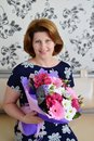 Positive woman with a bouquet of flowers in the room Stock Images