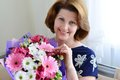 Positive woman with a bouquet of flowers in the room Royalty Free Stock Photos