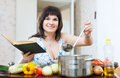 Positive woman cooking with cookery book and ladle in kitchen Royalty Free Stock Photos