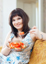 Positive woman eats veggie salad casual on sofa at home interior Stock Photography