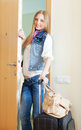 Positive woman in jeans with luggage blonde leaving her home Royalty Free Stock Photo