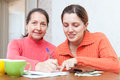 Positive women fills in utility payments bills two at home Royalty Free Stock Images