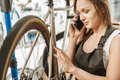 Positive worker repairing the bicycle and talking over the phone Royalty Free Stock Photo