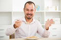 Positive young man eating porridge
