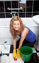 Positive young woman cleaning bathroom's floor Stock Image