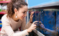 Positive young woman selecting aquarium fish