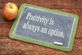 Positivity is always an option text on a slate blackboard against red barn wood Stock Image