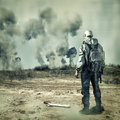 Post apocalypse man in gas mask explosions with handgun and back pack apocalyptic world looking on on horizon Stock Photography