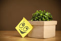 Post-it note with smiley face sticked on flowerpot