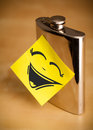 Post-it note with smiley face sticked on hip flask