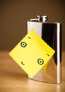 Post-it note with smiley face sticked on a hip flask