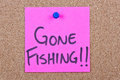 Post it note on wood in pink with gone fishing Stock Image