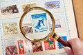 Postage sport stamp with skier under magnifier on album Royalty Free Stock Photo