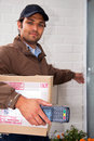 Postal worker at the door carrying a parcel and a portable atm rings a doorbell with a cash on delivery service Stock Images