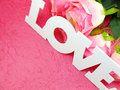 Postcard with artificial flowers and tag with words with love on pink background Royalty Free Stock Photo