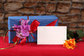 Postcard with gift with rose empty stands in front of decorative holiday box together yellow flower on red table on blurred stone Royalty Free Stock Photo