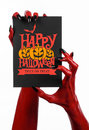Postcard and Happy Halloween theme: red devil hand with black nails holding a paper card with the words Happy Halloween on a white Royalty Free Stock Photo