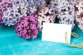 Postcard with splendid lilac flowers and empty tag for your text on aged wooden background Royalty Free Stock Images