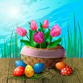 Postcard with tulips in a wicker basket and Easter eggs on a wooden table against the background of grass and sky