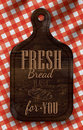 Poster with bread cutting brown wood board lettering fresh bread for you on a red checkered tablecloth Royalty Free Stock Image