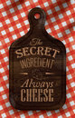 Poster with bread cutting brown wood board lettering the secret ingredient always cheese color on a red checkered tablecloth Royalty Free Stock Images