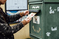 Posting letter to old postbox on street Royalty Free Stock Photo