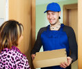 Postman delivered a parcel to girl Royalty Free Stock Photo