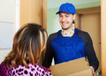 Postman in uniform delivered a parcel Royalty Free Stock Photo