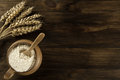 Pot of flour and wheat ears on wooden background. Royalty Free Stock Photo