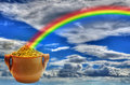 Pot of gold and rainbow filled with nuggets with sky background Stock Images