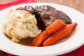 Pot roast with mashed potatoes delicious braised beef creamy and roasted carrots and rice gravy Royalty Free Stock Photos