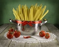 Pot with spaghetti and tomatoes Royalty Free Stock Photo