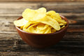 Potato chips in bowl on brown wooden background. Royalty Free Stock Photo