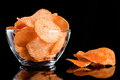 Potato chips in glass bowl, isolated on background Royalty Free Stock Photo