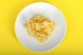 Potato crisps on a plate against yellow background Stock Images