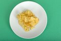 Potato crisps on a plate portion of against green background Stock Photography