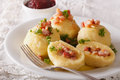 Potato dumplings stuffed with ham and onion close-up and lingonb Royalty Free Stock Photo