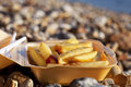 Potato fries in take out box on a sea  sea  beach Royalty Free Stock Images